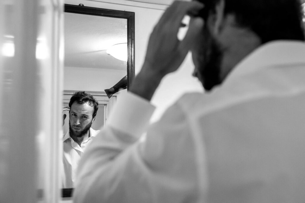 groom getting ready looking the mirror during the preparation of the wedding in sicily