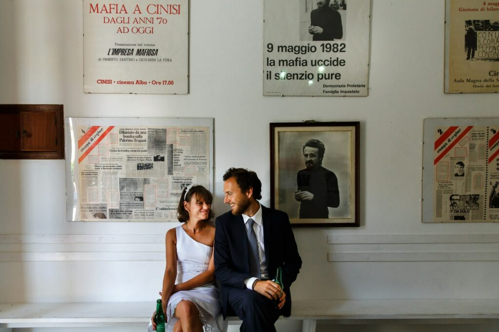 bride and groom having a beer and relaxing in the memorial house museum of peppino impastato