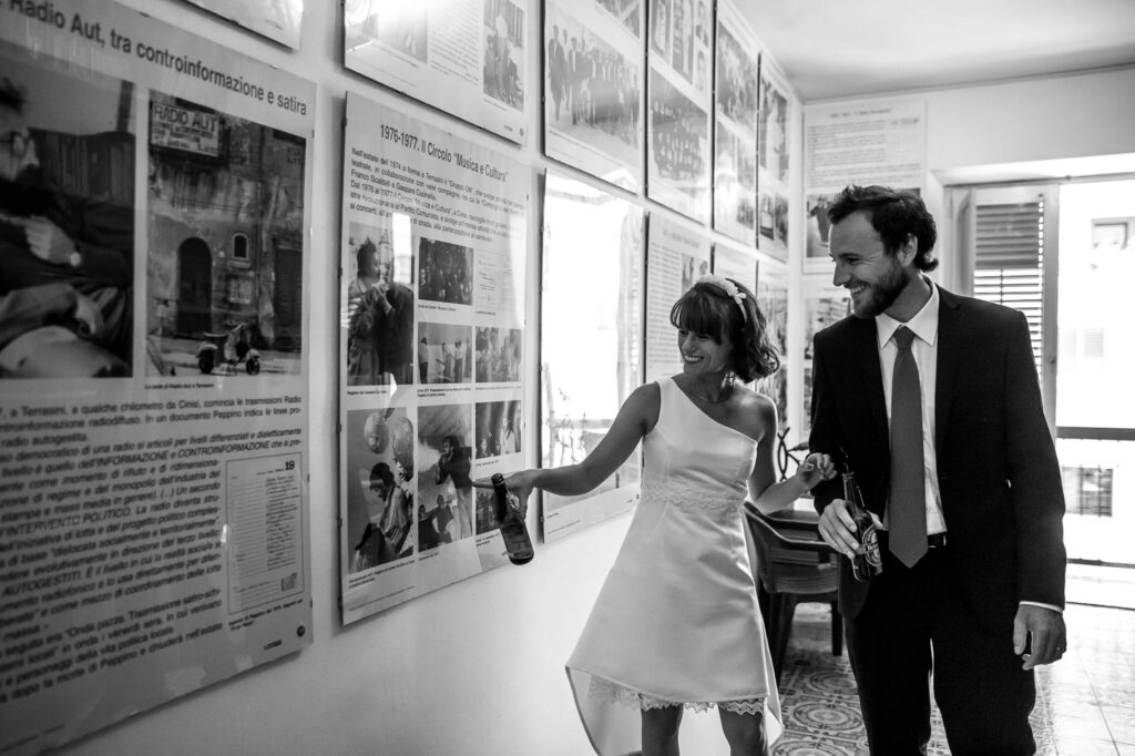 bride and groom having a beer and visiting the memorial house museum of peppino impastato