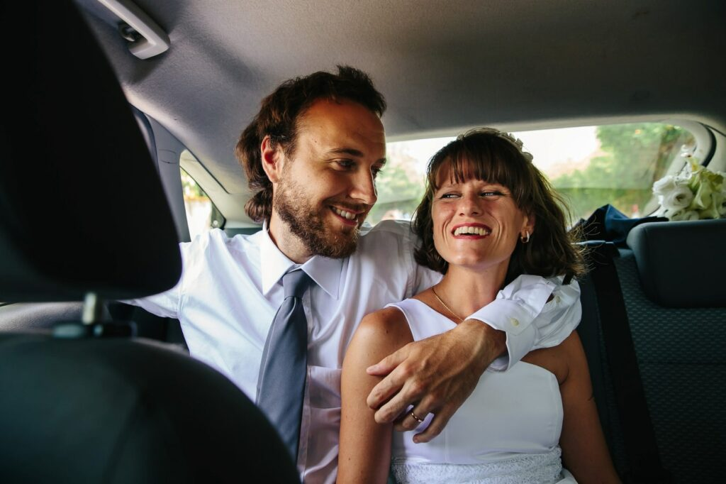 bride and groom hugging in the car