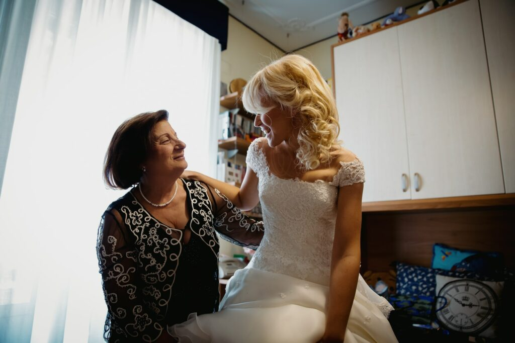 mother of the bride helping the bride getting dressed in a photo captured by villa miani wedding photographer