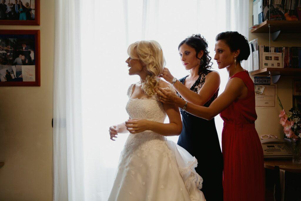 bride is wearing wedding dress helped by bridesmaid