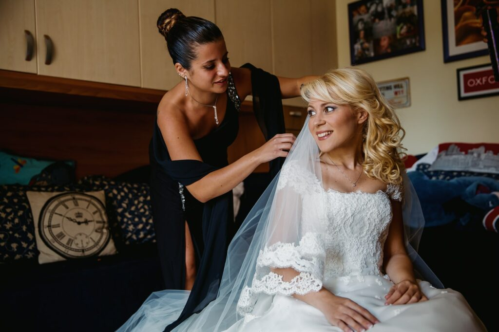 bride is putting the veil on before going to wedding ceremony