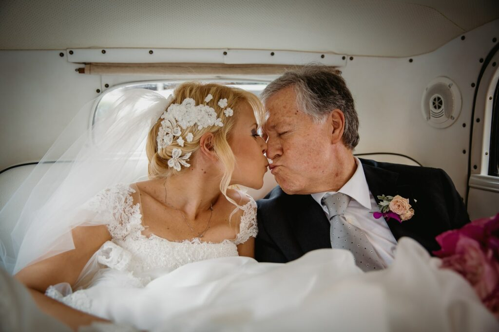 bride and father of the bride kiss in the car