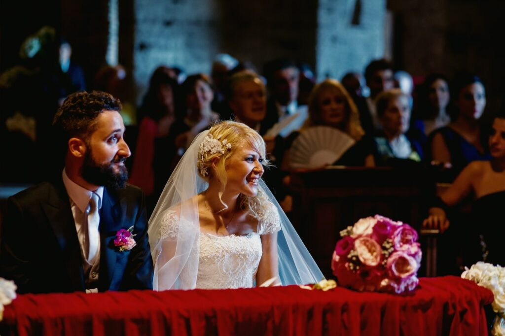 bride and groom sitting in front of the altar photographed by the villa miani wedding photographer