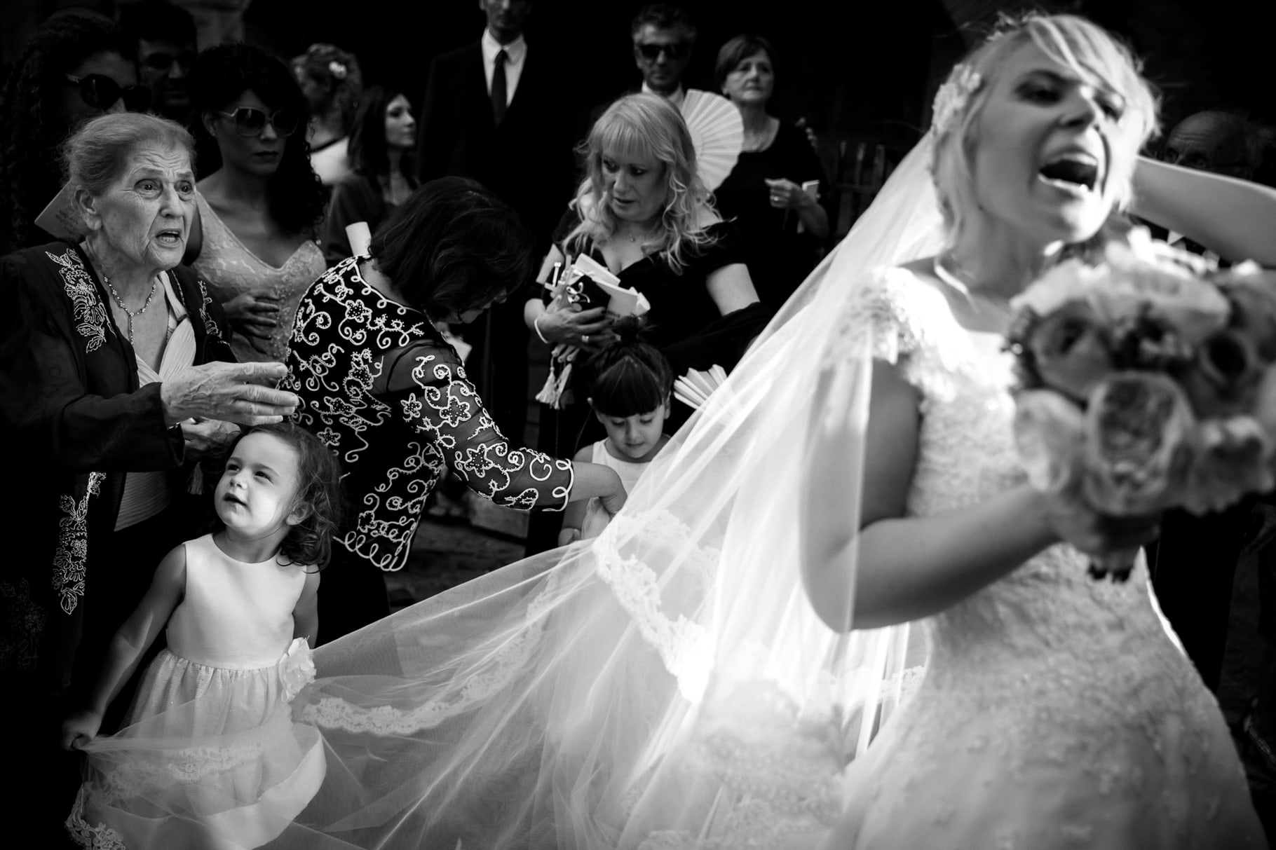 funny moment of a kid pulling the bride veil after the ceremony in a photo captured by villa miani wedding photographer