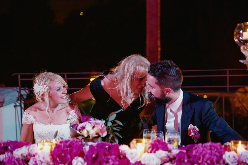 bride and groom at the table with grooms mom in a photo captured by villa miani wedding photographer