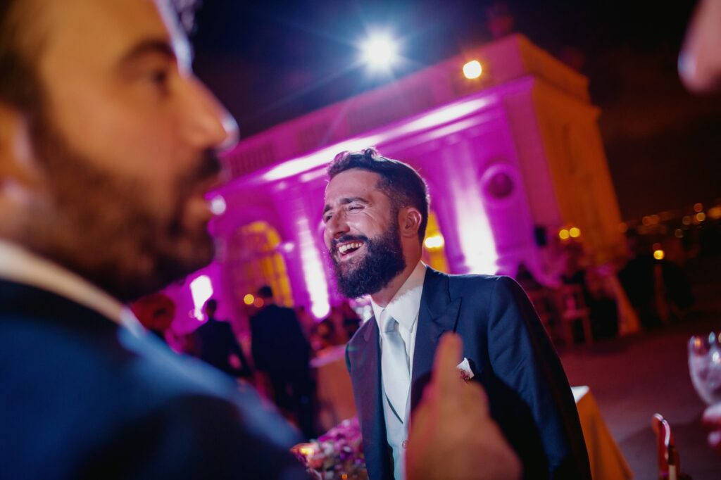 groom laughing at wedding reception in villa miani
