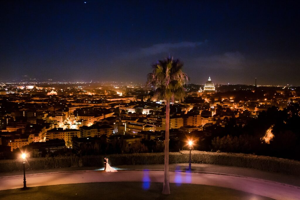 portrait of newlyweds with panorama of rome at night at villa miani