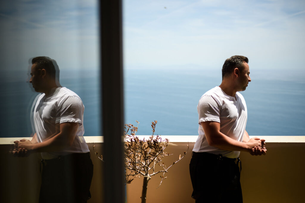 groom staring at the sea in positano amalfi coast before wedding