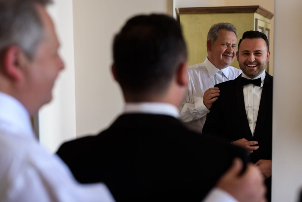 groom getting dressed in the hotel room in front of the mirror