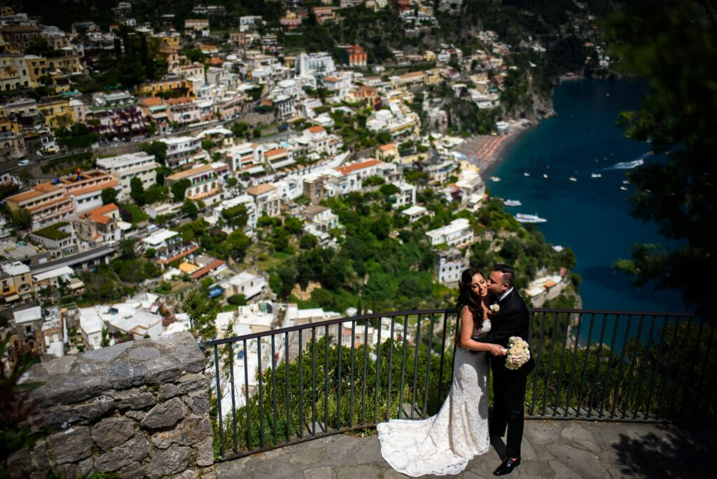 couple portrait of bride and groom with a panoramic view of positano in the background