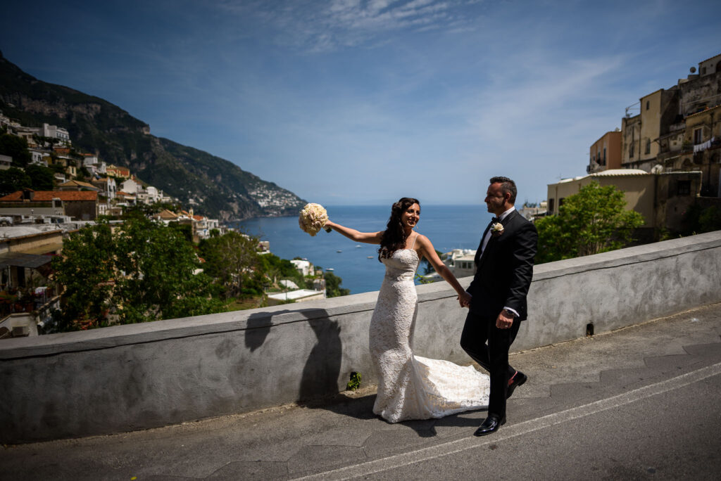 the bride and groom stroll through the streets of positano before their intimate rada positano amalfi coast wedding