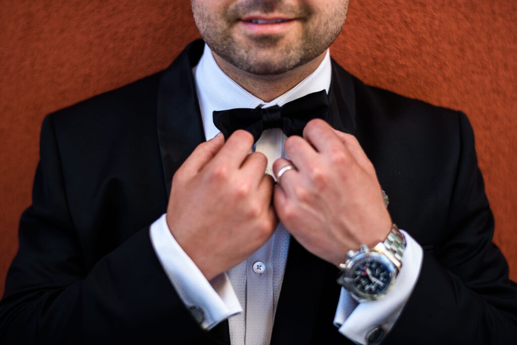 the grooms bow tie with detail of the hands
