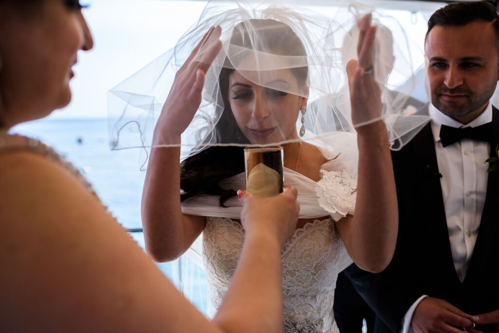 bride drinking the wine during the traditional jewish wedding ceremony at the rada restaurant of positano