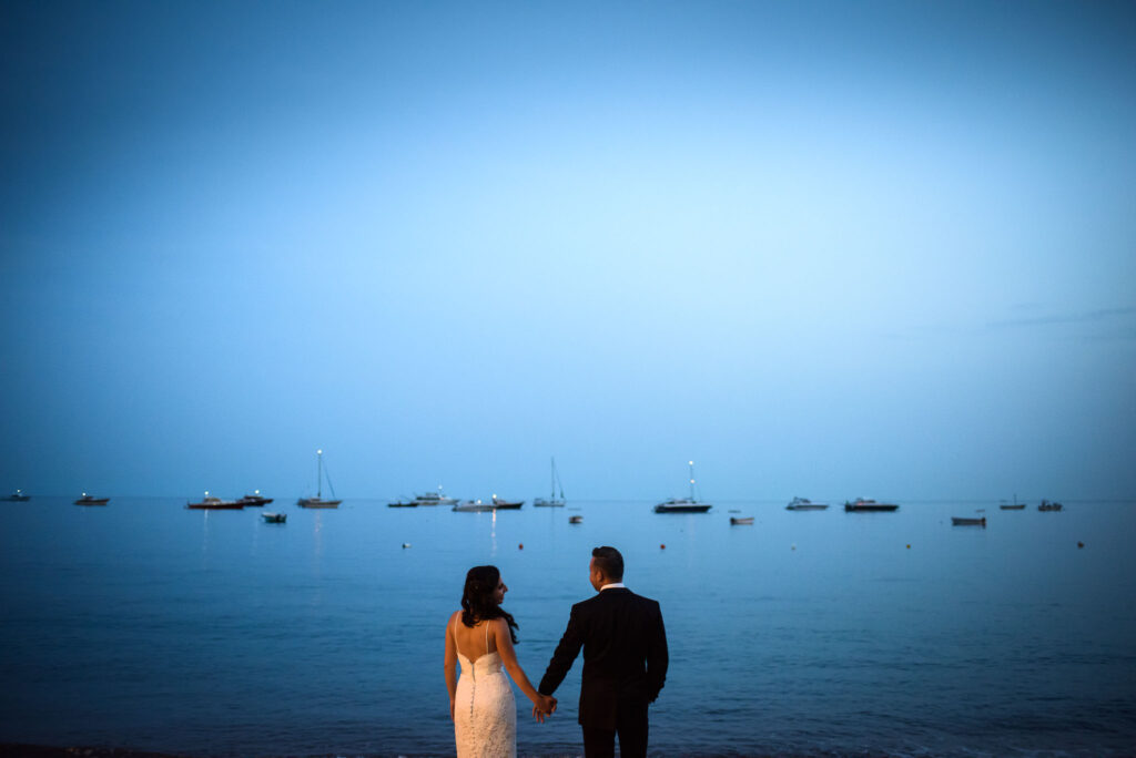 the bride and groom hold hands in front of the sea of positano