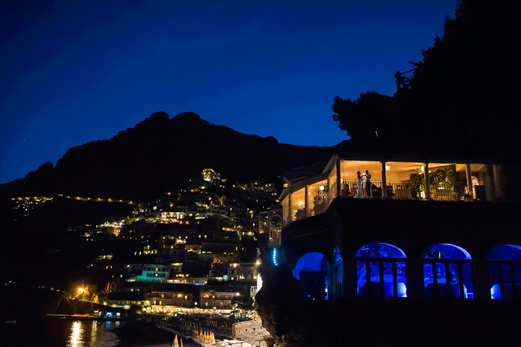 view of positano illuminated at night with the rada restaurant in the foreground