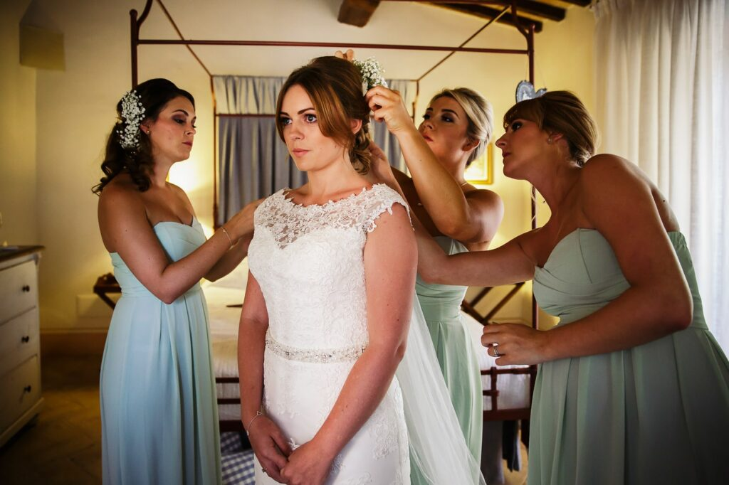 the bride wears the dress and the bridesmaids help her put on the veil