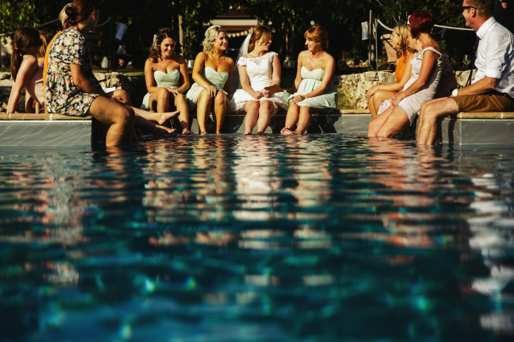 bride and her friends by the pool during umbria destination wedding reception