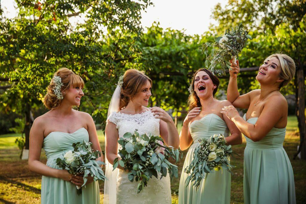 bride and bridesmaid having fun in the garden of borgo della marmotta