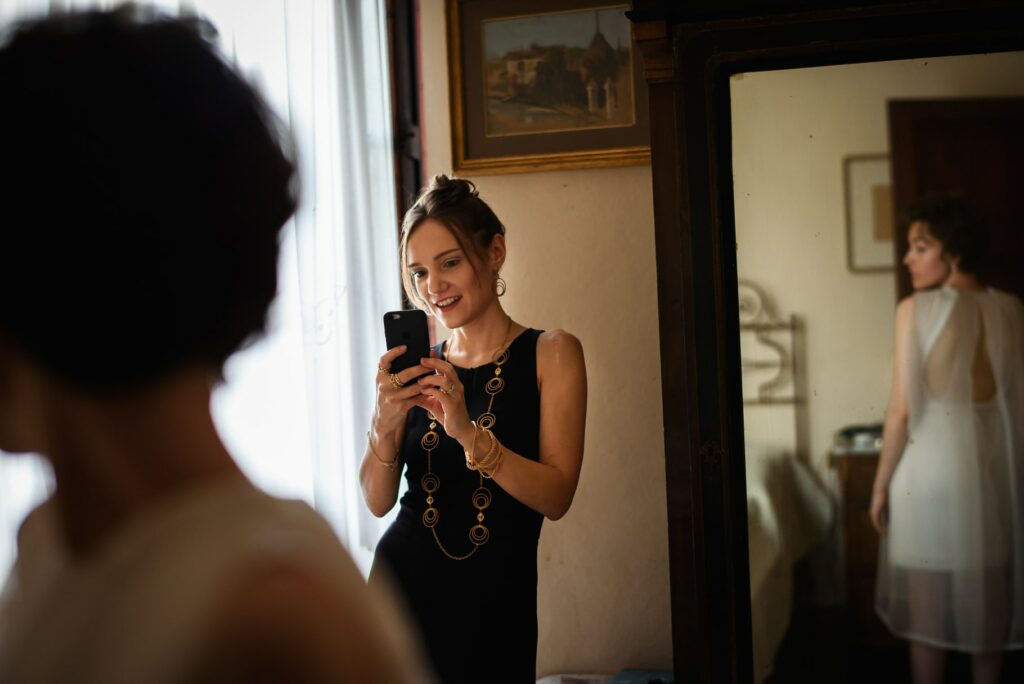 bride facing in the mirror while her friend is taking a snap as tuscany wedding photographer