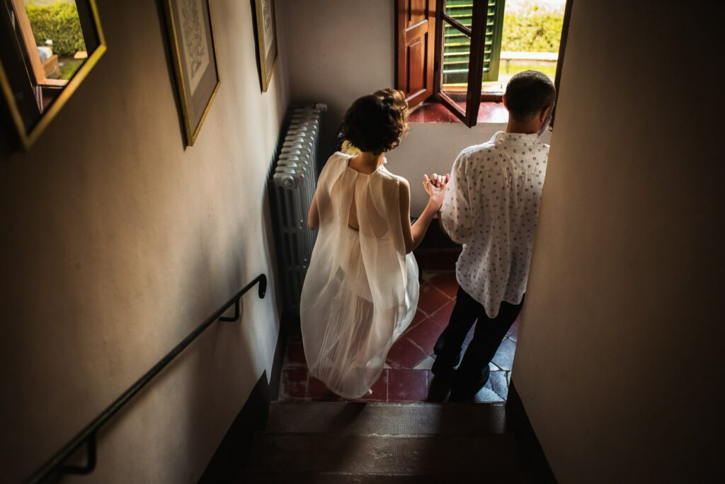 the bride and her father descending the stairs to go to the wedding ceremony in tuscany