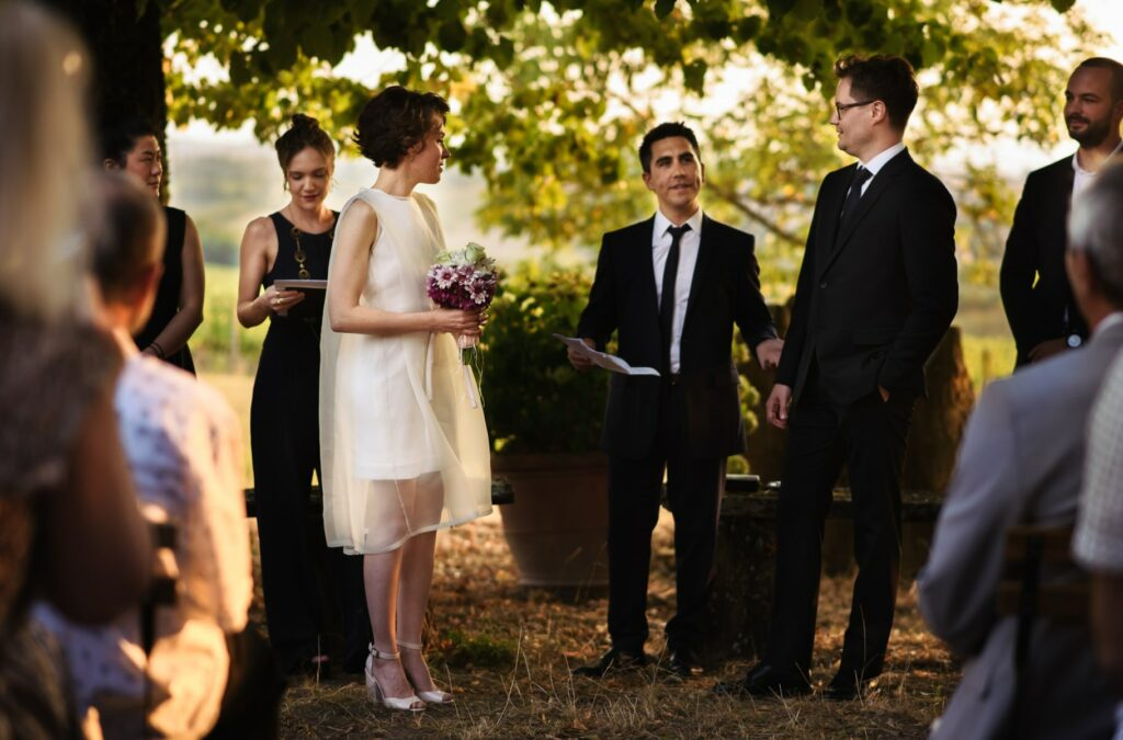 the bride and groom with the celebrant during the outdoor wedding ceremony in tuscany