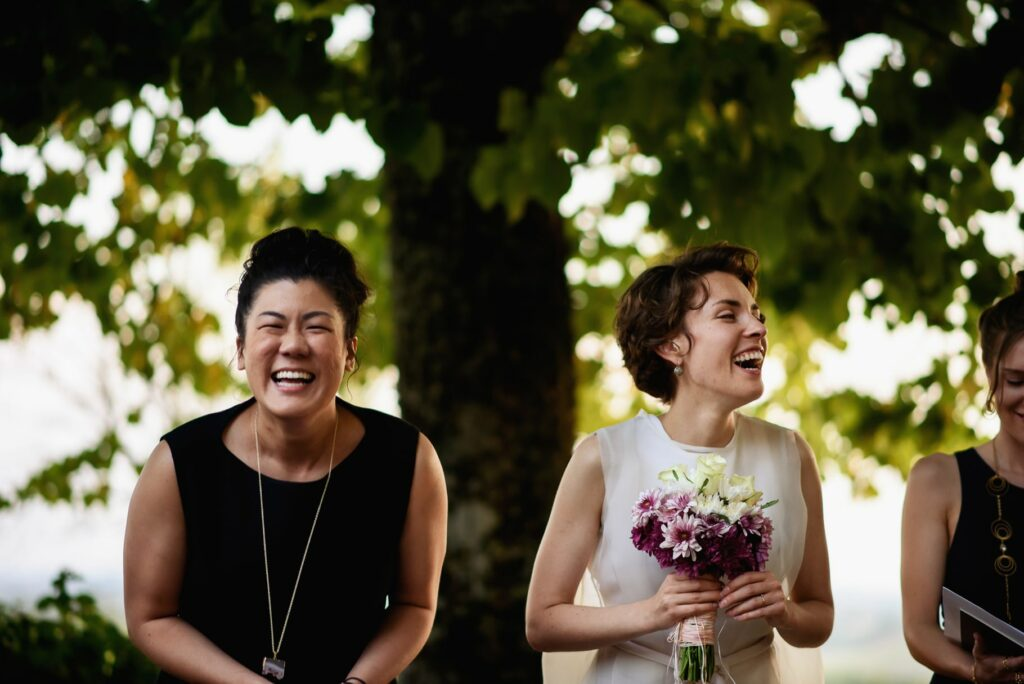 bride and bridesmaid laughing at outdoor symbolic wedding ceremony in an image captured by tuscany wedding photographer
