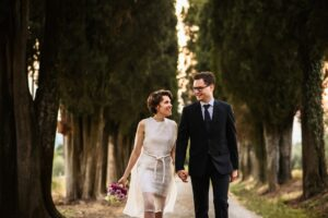 bride and groom walking hand in hand after the wedding ceremony in tuscany