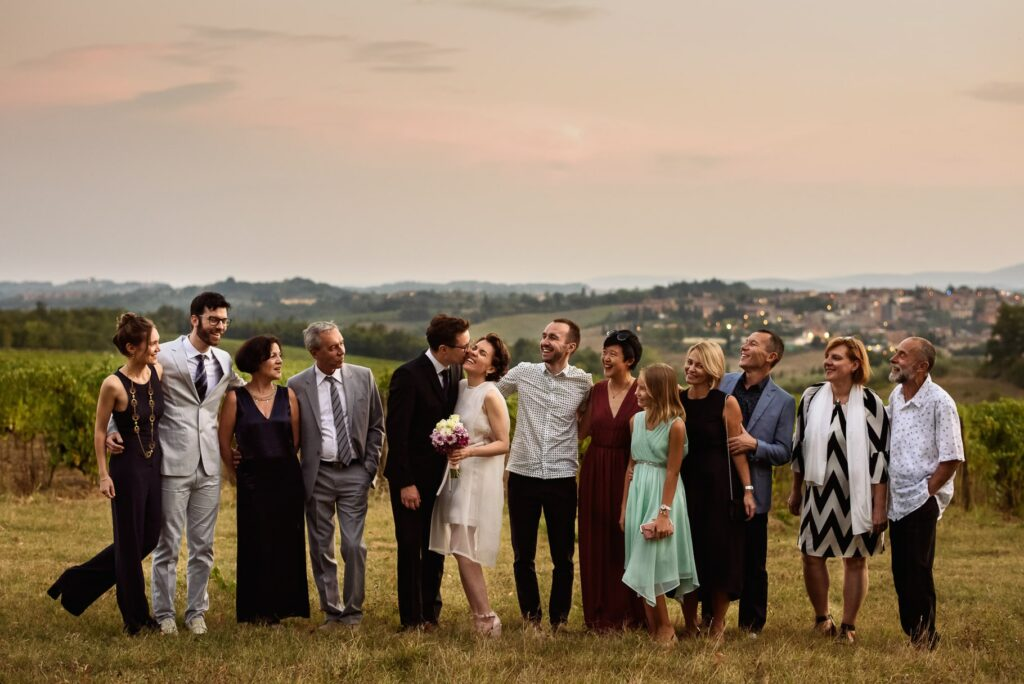 group photo of the newlyweds with family and friends taken by the tuscany wedding photographer