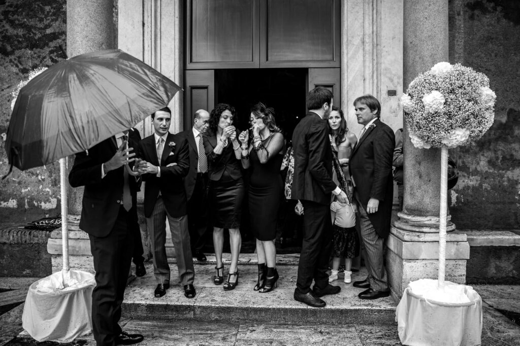 wedding guests await the bride outside the church