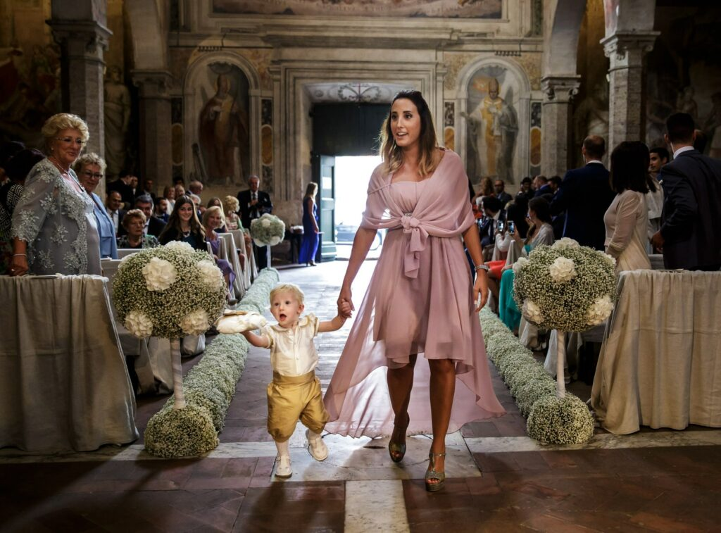 bridesmaid and page boy enter the church