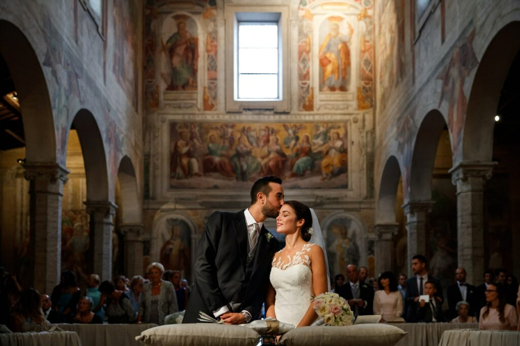 groom kissing bride in the church