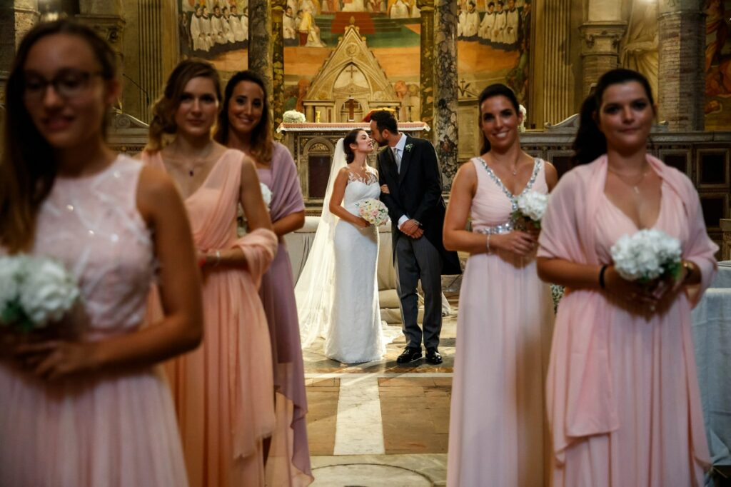 bride and groom kiss in church with bridesmaids before going to celebrate the wedding at villa miani