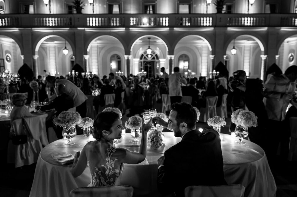 bride and groom toasting at the table during the wedding at villa miani