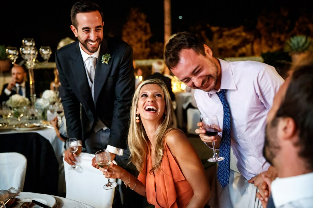 groom chatting and having fun with friends during wedding dinner at villa miani