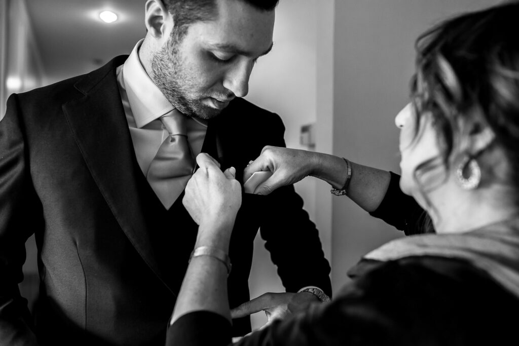 groom getting ready with the help of his mother for jewish wedding in rome