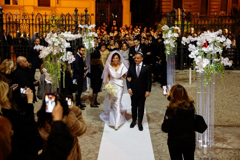 bride and dad approaching the entrance to rome synagogue for a jewis wedding