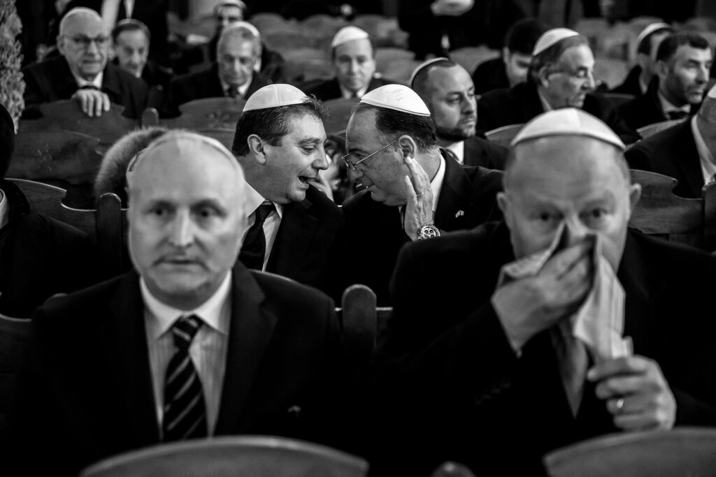 jewish wedding male guests sitted in the synagouge waiting for the jewish ceremony to start