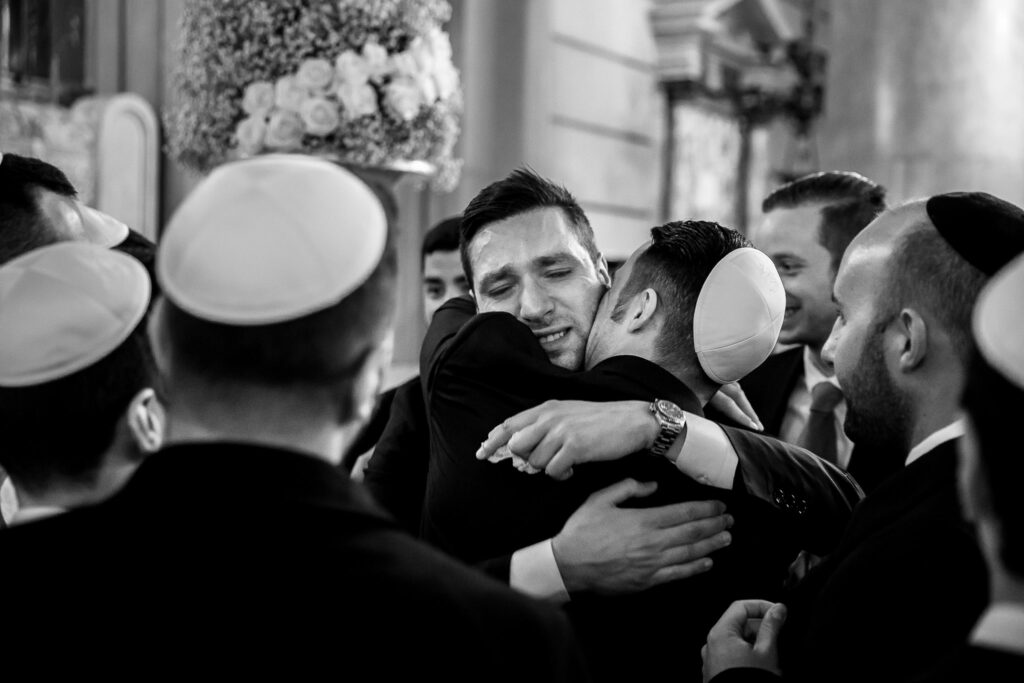 groom hugging a friend after the ceremony in the synagogue