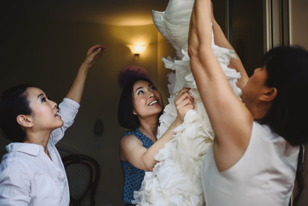 bride taking the dress helped by bridesmaid