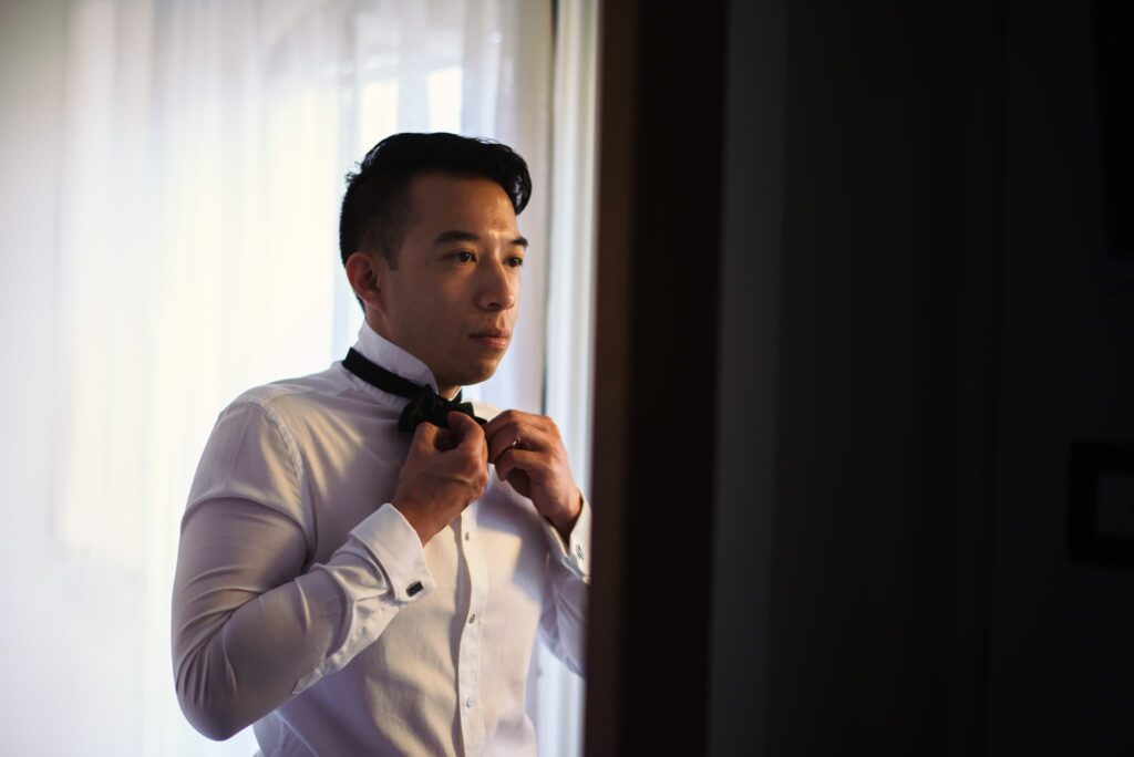 groom wearing bow tie in front of the mirror