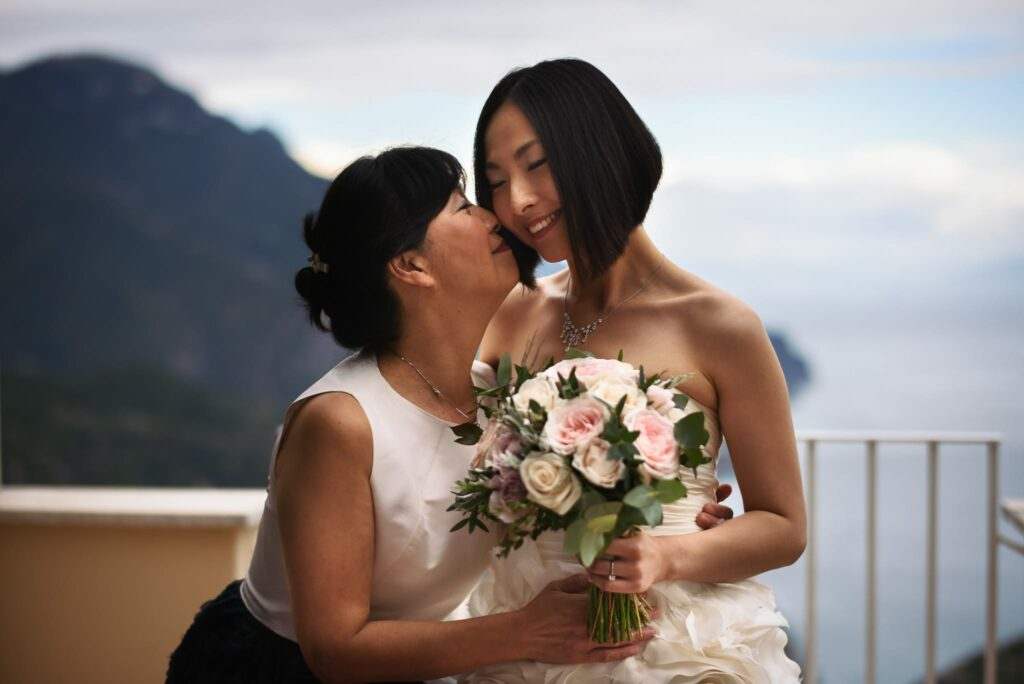 bride with dress and bouquet kissing her mom