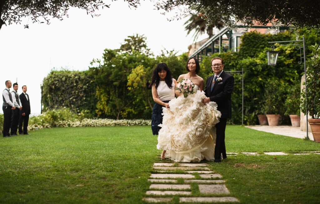 bride entering the wedding ceremony venue wagner gardens at hotel caruso in ravello with her parents