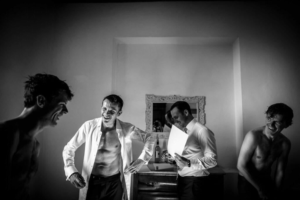 groom getting dressed with best men before the wedding in villa gamberaia florence