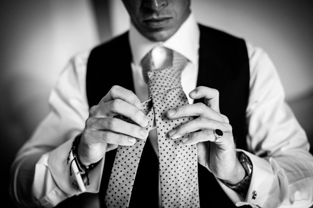 detail of groom while he ties the knot