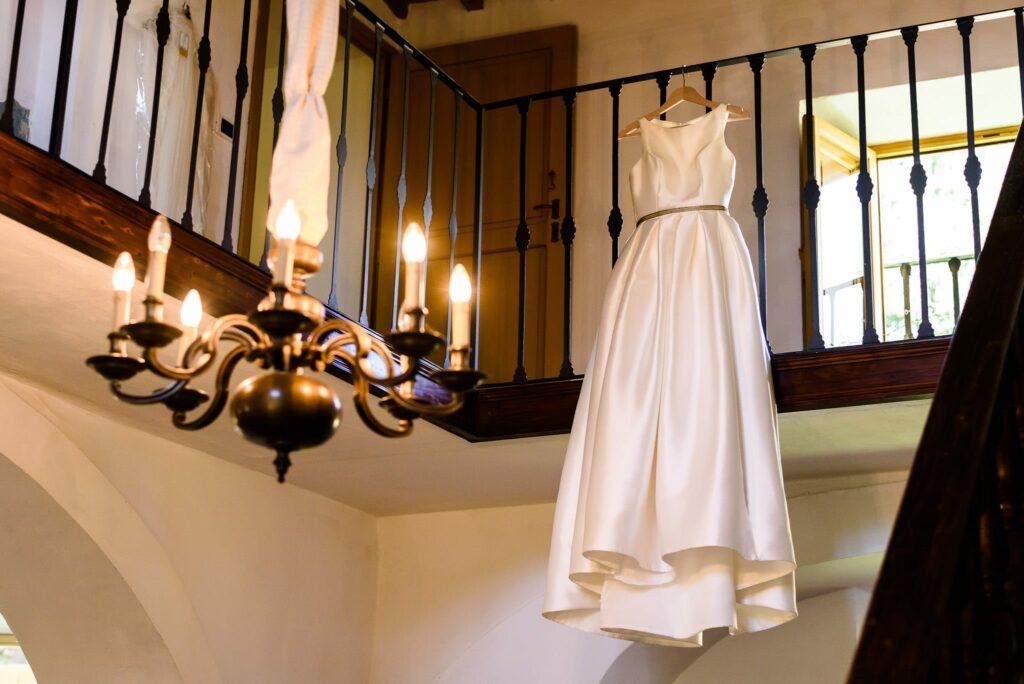 bride wedding dress hanging from the balcony at wedding in villa gamberaia