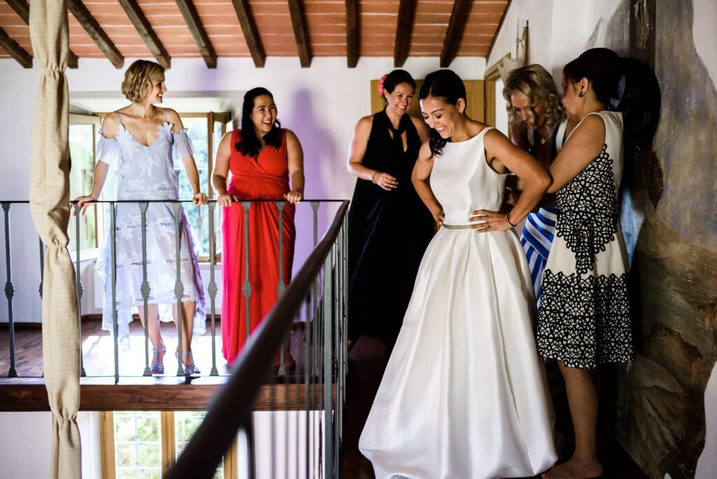 bride getting ready and dressed with friends family and bridesmaid at wedding in villa gamberaia