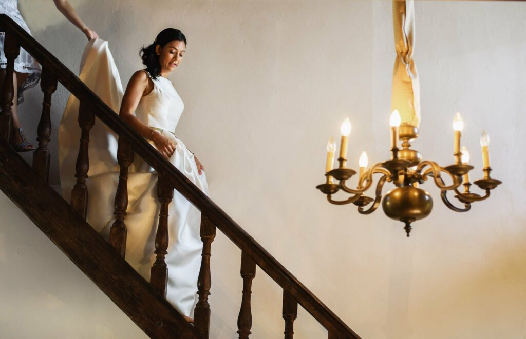 bride with her wedding dress walkind down the stairs