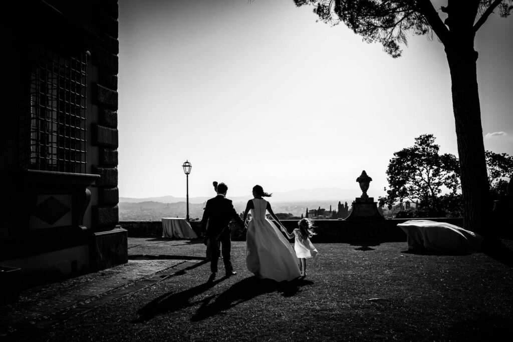 the bride and groom from behind with a little girl at villa gamberaia